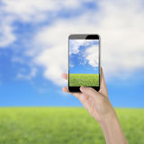 Female hand holding smart phone with thumb pushing button Stock Photography