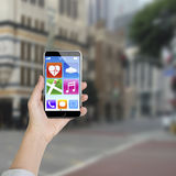 Female hand holding smartphone with app icons Royalty Free Stock Photography