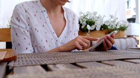 Female hand holding smartphone, in a cafe or restaurant stock video