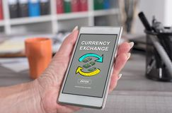 Currency exchange concept on a smartphone. Female hand holding a smartphone with currency exchange concept Stock Photos