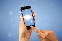 Female hand holding smartphone. Female fingers touching smartphone with cloud concept Royalty Free Stock Photos