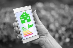 Home energy efficiency concept on a smartphone. Female hand holding a smartphone with home energy efficiency concept royalty free stock photos