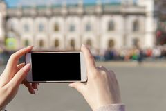 Female hand holding smartphone take photo crowd.  royalty free stock photo