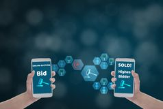 Female hand holding smartphone to Enter the price for bid,via wireless network on blue bokeh background with auction icon, Concept royalty free stock image