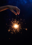 Female Hand holding a sparkler. On dark background Royalty Free Stock Photos