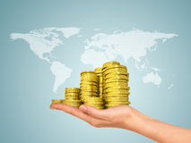 Female hand holding stack of gold coins Royalty Free Stock Image