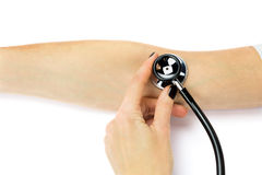 Female hand holding stethoscope on arm of patient Royalty Free Stock Images