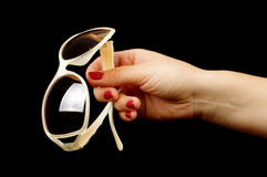 Female hand holding stylish sunglasses on the black background Royalty Free Stock Photography