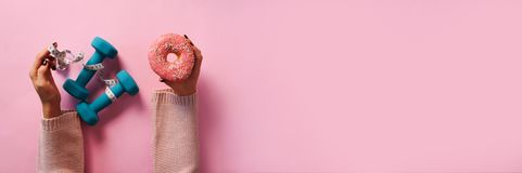 Female hand holding sweet donut, measuring tape, dumbbells over pink background. Top view, flat lay. Weight lost, sport, fitness, stock photography