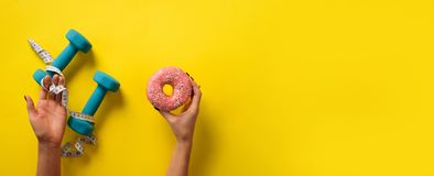 Female hand holding sweet donut, measuring tape, dumbbells over yellow background. Top view, flat lay. Weight lost, sport, fitness. Diet concept. Banner with royalty free stock images