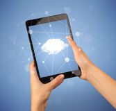 Female hand holding tablet. Female fingers touching tablet with cloud concept Royalty Free Stock Image