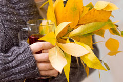 Female hand holding tea and autumn leaves Royalty Free Stock Photo