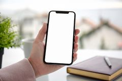 Female hand holding touch phone with screen above the table in cafe stock photography