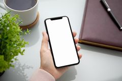 Female hand holding touch phone with screen above the table in the office stock image