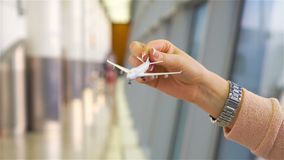 Female hand holding toy airplane, copy space for text. Passenger with small model airplane at the airport. SLOW MOTION. Close up hand holding an airplane model stock video