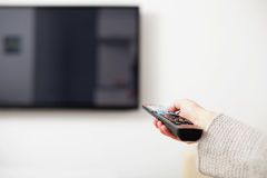Female hand holding TV Remote Control Royalty Free Stock Photos