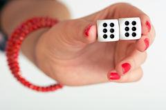 A female hand holding two dices and showing double six. Close up photo of a female hand holding two dices and showing double six Stock Photos