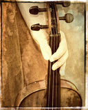 Female hand holding violin vintage look. A vintage looking photograph of a female hand holding a violin, with a vintage border and texture colouring Royalty Free Stock Images