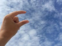 Female hand holding virtual card or blank paper against blue sky. A female hand holding virtual business card or blank paper against blue sky Stock Photography