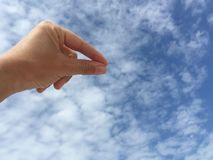 Female hand holding virtual card or blank paper against blue sky. A female hand holding virtual business card or blank paper against blue sky Royalty Free Stock Image