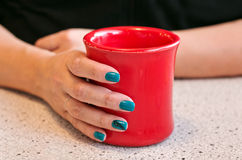 Female Hand holding a warm red cup of coffee Stock Image