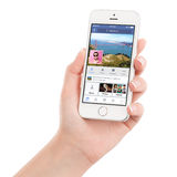 Female hand holding white Apple iPhone 5s with Facebook app Royalty Free Stock Photos