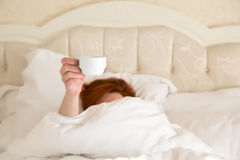 Female hand holding white Coffee Cup Queen Size Vintage Bed. Demanding her Morning Coffee white Blanket warm tone background stock photos