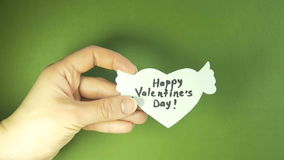 Female hand holding white paper heart with wings on green background - Happy Valentine`s Day stock video