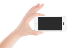 Female hand holding white smart phone in landscape orientation. Female hand holding white modern smart phone with blank screen in landscape orientation. Isolated Royalty Free Stock Photo