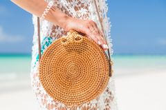 Female hand holding wicker bag on the seashore. Concept vacation, travel. Sexy tanned young woman in blue bikini posing on the sea. Beautiful model sunbathes and stock photography