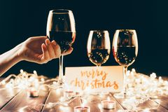 Wineglasses and christmas decorations. Female hand holding a wine glass over wooden table with fairylights, candles and merry christmas card Royalty Free Stock Photo