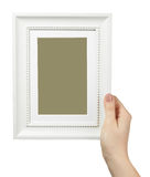 Female hand holding a wooden frame isolated on white background. Stock Photos