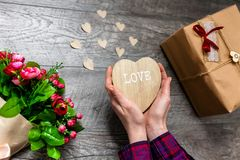 Female hand holding a wooden heart, Valentine`s Day, romantic photos . with a gift and a bouquet of flowers, with hearts and gift. S, suitable for advertising royalty free stock image