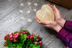 Female hand holding a wooden heart, Valentine`s Day, romantic photos . with a gift and a bouquet of flowers, with hearts and gift. S, suitable for advertising stock image