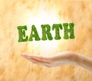 Female hand holding word earth made of grass Stock Photo