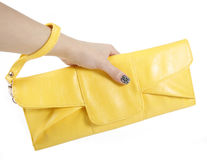 Female hand holding yellow clutch bag. Isolated on white stock image
