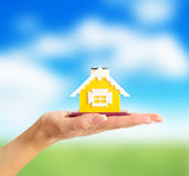 Female hand holding a yellow house on field background Stock Image