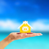 Female hand holding a yellow house on sea background Royalty Free Stock Images