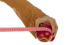 The female hand holds an apple. And tailor's meter royalty free stock photos