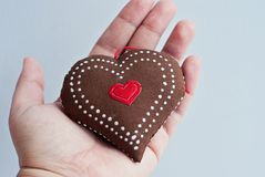 Female hand holds a beautiful soft handmade heart. On the white background Valentine`s day concept stock photography