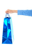 Female hand holds blue gift bag, isolated Stock Image