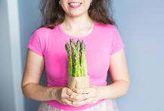 Female hand holds Bundle of green asparagus. Concept of vegans, vegetarians and healthy food.  Royalty Free Stock Photography