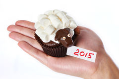 Female hand holds cake lamb as simbol 2015 new years isolated Stock Photos