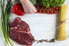 A female hand holds cherry tomatoes. Fresh raw meat beef steak w. A female hand holds cherry tomatoes. Fresh raw meat beef steak. Flat lay Stock Photography