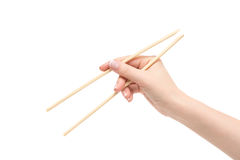 Female hand holds chopsticks on a white background. Isolated female hand holds chopsticks on a white background Stock Photos