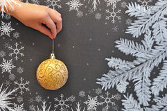 Female hand holds a Christmas ball against the background of a chalkboard Royalty Free Stock Images