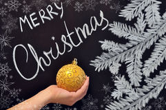 The female hand holds a Christmas ball on a chalkboard Stock Photography