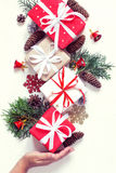 Female hand holds Christmas gift boxes collection And decor. Vintage toning Royalty Free Stock Photo