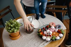 Female hand holds coffee beans and saves from falling down. Beautiful and colorful mix of zephyr and fruits on a table royalty free stock image