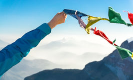 Female hand holds colored flags. Happy success reaching mountain summit. stock image